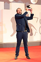 """VENICE, ITALY - SEPTEMBER 11: Director Kiro Russo poses with the Special Orizzonti Jury Prize for """"El Gran movimento"""" attends the awards winner photocall during during the 78th Venice International Film Festival on September 11, 2021 in Venice, Italy."""