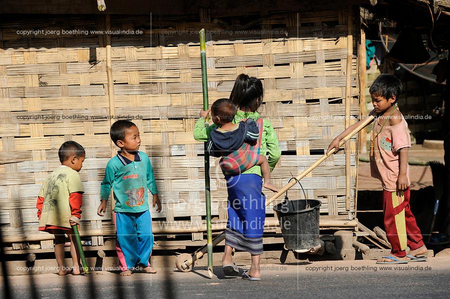 LAO PDR, province Oudomxay , village Houyta, ethnic group Khmu, boy transport water bucket with bamboo roller / LAOS Provinz Oudomxay Dorf Houyta , Ethnie Khmu , Junge transportiert Wassereimer mit Bambus Roller