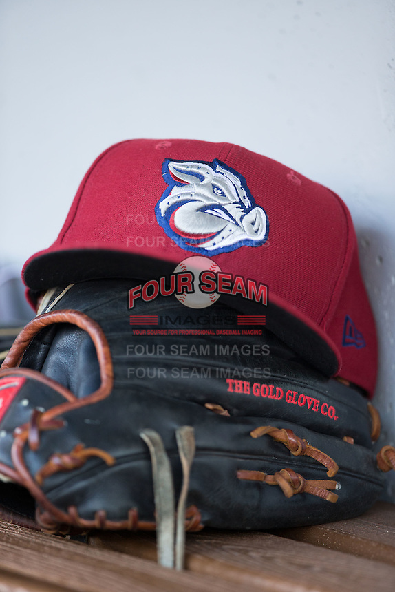 A Lehigh Valley Iron Pigs hat sits atop a Rawlings baseball glove in the visitors dugout during the game against the Charlotte Knights at BB&T BallPark on June 3, 2016 in Charlotte, North Carolina.  The Iron Pigs defeated the Knights 6-4.  (Brian Westerholt/Four Seam Images)