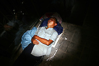 CHINA. Beijing. A homeless man sleeping on the sidewalk in the shopping district of Xidan . 2008
