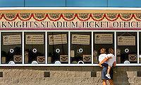 A mother and son buy tickets to a Charlotte Knights baseball game.