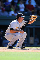 Manager Luis Dorante (25) of the Charleston RiverDogs warms up the pitcher between innings in a game against the Greenville Drive on Sunday, June 28, 2015, at Fluor Field at the West End in Greenville, South Carolina. Charleston won, 12-9. (Tom Priddy/Four Seam Images)