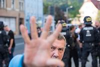"""Ca. 500 Menschen demonstrierten am Freitag den 31. Juli 2015 im Saechsischen Feital gegen Rassismus und fuer die Aufnahme von Fluechtlingen.<br /> Nach mehreren Wochen rassistischer Uebergriffe und Bedrohungen durch einen Teil der Freitaler Bevoelkerung war dies ein Zeichen der Solidaritaet mit den gefleuchteten Menschen.<br /> Am Rande der Demonstration kam es immer wieder zu rassistischen Poebeleien, Flaschenwuerfen und versuchten Angriffen auf die Demonstranten durch Neonazis und Hooligans die sich vor ihrer Stammkneipe """"Timba"""" versammelt hatten. Vereinzelt ging die Polizei gegen die Rechten vor und nahm mindestens eine Person wegen zeigen eines Hitlergrusses fest. Die Flaschenwuerfe blieben fuer die Rechten folgenlos.<br /> Im Bild: Ein Rechter greift den Fotografen an.<br /> 31.7.2015, Freital/Sachsen<br /> Copyright: Christian-Ditsch.de<br /> [Inhaltsveraendernde Manipulation des Fotos nur nach ausdruecklicher Genehmigung des Fotografen. Vereinbarungen ueber Abtretung von Persoenlichkeitsrechten/Model Release der abgebildeten Person/Personen liegen nicht vor. NO MODEL RELEASE! Nur fuer Redaktionelle Zwecke. Don't publish without copyright Christian-Ditsch.de, Veroeffentlichung nur mit Fotografennennung, sowie gegen Honorar, MwSt. und Beleg. Konto: I N G - D i B a, IBAN DE58500105175400192269, BIC INGDDEFFXXX, Kontakt: post@christian-ditsch.de<br /> Bei der Bearbeitung der Dateiinformationen darf die Urheberkennzeichnung in den EXIF- und  IPTC-Daten nicht entfernt werden, diese sind in digitalen Medien nach §95c UrhG rechtlich geschuetzt. Der Urhebervermerk wird gemaess §13 UrhG verlangt.]"""