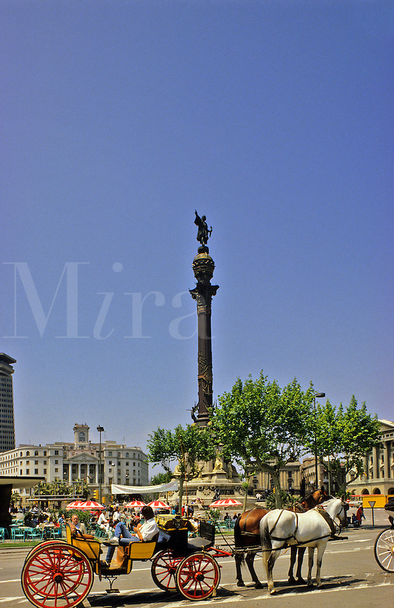 Barcelona, Spain.  Statue of Columbus in Placa del Portal de la Pau and horsedrawn carriage.