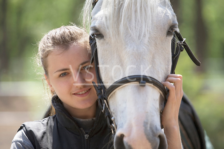 Portrait of young  woman embracing horse