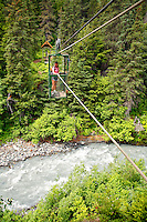 A hiker pulls herself across Glacier Creek on the aerial hand tram, Winner Creek Gorge Trail, Girdwood, Chugach National Forest, Alaska.