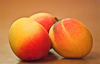 Three ripe mangos sitting on countertop