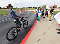 """SCHOOL BIKING CHAMPIONS<br />Students and faculty at Willowbrook Elementary in Bentonville, including Principal Christina Hamilton (right), greet Tom Walton, co-founder of the Runway Group, who delivered by bicycle a $5,000 grant to the school. Willowbrook won the """"Bike Bentonville Schools"""" challenge, a contest in the Bentonville School District during September to encourage students to ride their bikes to school. Willowbrook won the prize by increasing bike ridership among students by 77 percent during September. Eighteen schools took part in the contest and each school that raised student biking percentage received $2,500. The contest was a partnership of the Runway Group and Bentonville schools, with philanthropic support from Tom and Steuart Walton. OZ Trails donated 20 bike racks to Willowbrook and principal Hamilton plans to buy more with the grant money. Go to nwaonline.com/211007Daily/ to see more photos. <br />(NWA Democrat-Gazette/Flip Putthoff)"""