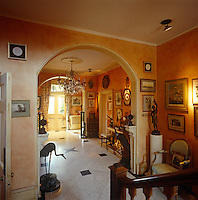 This spacious entrance hall is filled with an interesting collection of furniture, paintings and sculpture