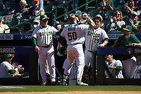 Mack Mueller (50) of the Baylor Bears is greeted by teammate Andy Thomas (25) as he returns to the dugout after hitting a home run against the Missouri Tigers in game one of the 2020 Shriners Hospitals for Children College Classic at Minute Maid Park on February 28, 2020 in Houston, Texas. The Bears defeated the Tigers 4-2. (Brian Westerholt/Four Seam Images)