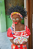 Praia do Forte, Bahia State, Brazil. Sculpture of a traditional Bahiana woman. Afro hair, green eyes, red dress, holding plate.