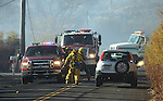 Firefighters evacuate neighbors as a 400-acre brush fire burns in south Reno, Nev., on Friday, Nov. 18, 2011. More than 25 homes have been lost as high winds with gusts up to 60 mph drive the flames.  (AP Photo/Cathleen Allison)