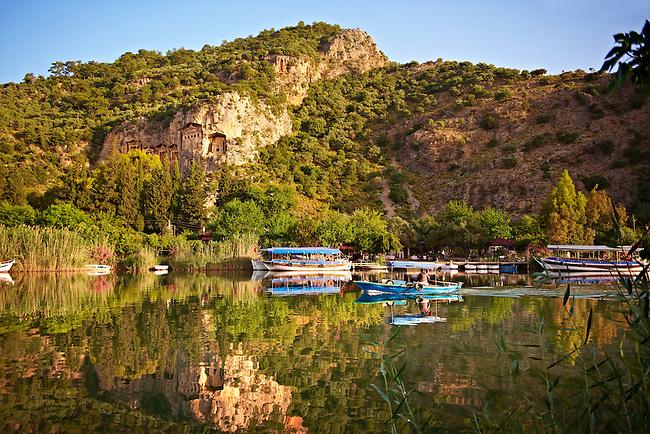 Boats on Dalyan Çayı River with Lycian Rock Tombs in the cliffs . Mediterranean coast Turkey