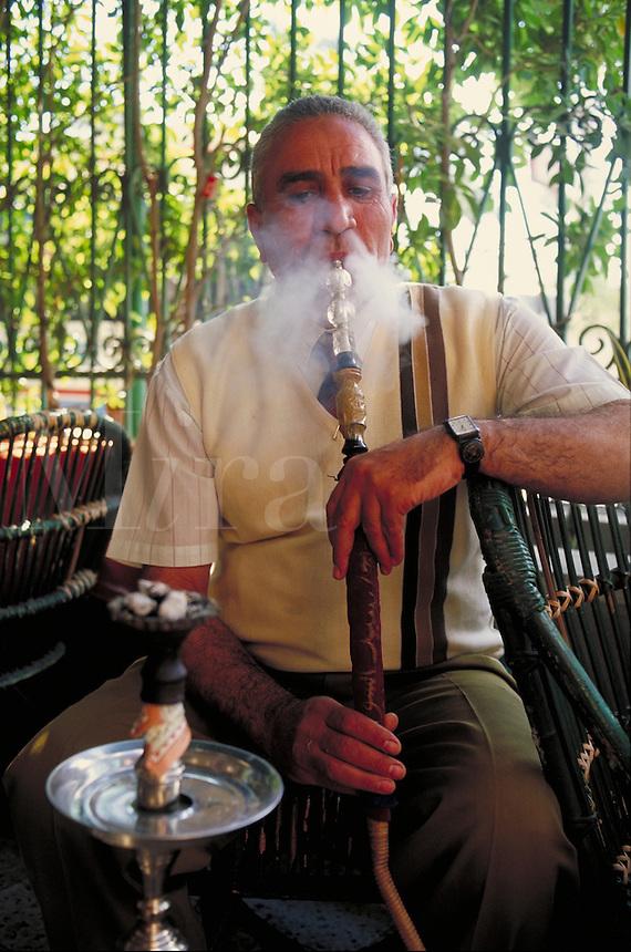 man smoking water pipe in restaurant