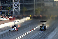 Apr 11, 2015; Las Vegas, NV, USA; NHRA top fuel driver Brittany Force (right) races alongside Clay Millican during qualifying for the Summitracing.com Nationals at The Strip at Las Vegas Motor Speedway. Mandatory Credit: Mark J. Rebilas-
