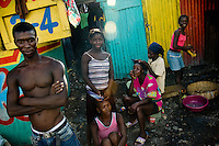 Young Haitian girls style their hair in a shanty town inside the La Saline market, Port-au-Prince, Haiti, 22 July 2008. Every day thousands of women from all over the city of Port-au-Prince try to resell supplies and food from questionable sources in the La Saline market. The informal sector significantly predominate within the poor Haitian economics and the regular shops virtually do not exist. La Saline is the largest street market area in Port-au-Prince.