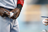Brandon Phillips of the Cincinnati Reds signs a baseball before a game against the Los Angeles Dodgers in a 2007 MLB season game at Dodger Stadium in Los Angeles, California. (Larry Goren/Four Seam Images)