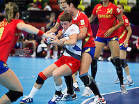 25 JUL 2012 - LONDON, GBR - Lyn Byl (GBR) (centre in white, blue and red) of Great Britain finds her path to goal blocked by the Spanish defence during the women's London 2012 Olympic Games warm up handball match in The Copper Box in the Olympic Park, in Stratford, London, Great Britain (PHOTO (C) 2012 NIGEL FARROW)