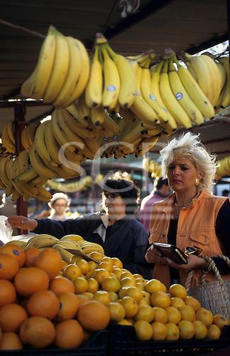 Belgrade, Serbia, Yugoslavia. Woman in an orange gilet buying fruit at the market.