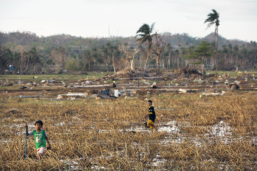 Philippines. Province Eastern Samar. Hernani. 95 % of the town was destroyed by typhoon Haiyan's winds and storm surge. Two boys walk in the destroyed rice fields and look for items to collect and recycle. Typhoon Haiyan, known as Typhoon Yolanda in the Philippines, was an exceptionally powerful tropical cyclone that devastated the Philippines. Haiyan is also the strongest storm recorded at landfall in terms of wind speed. Typhoon Haiyan's casualties and destructions occured during a powerful storm surge, an offshore rise of water associated with a low pressure weather system. Storm surges are caused primarily by high winds pushing on the ocean's surface. The wind causes the water to pile up higher than the ordinary sea level. 25.11.13 © 2013 Didier Ruef