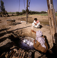 Pakistan. Sind.  Technician and local farmer test the quality of water from a new artesian well