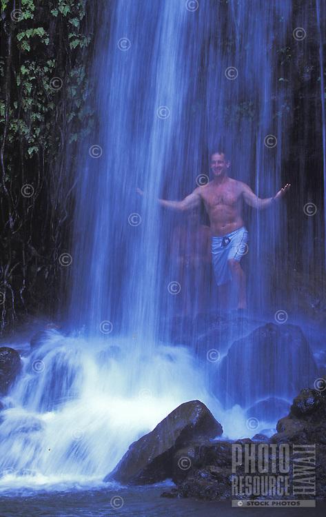 Men at a waterfall on the Kalihiwai River, North Shore of Kauai
