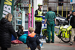 © Joel Goodman - 07973 332324 . 06/04/2017 . Manchester , UK . A bicycle paramedic responds to a call to help a woman , who is slouched and unresponsive in front of Max Spielmann photographic , in Piccadilly Gardens . An epidemic of abuse of the drug spice by some of Manchester's homeless population , in plain sight , is causing users to experience psychosis and a zombie-like state and is daily being witnessed in the Piccadilly Gardens area of Manchester , drawing large resource from paramedic services in the city centre . Photo credit : Joel Goodman