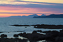 Looking out to the Isle of Rum at sunset, Isle of Mull, Scotland, UK. June.