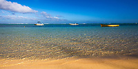 Beautiful gold sand beach with turquoise Indian Ocean water and fishing boats, at the foot of Le Morne Brabant mountain, Mauritius Island, Africa