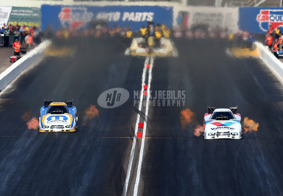 Feb 23, 2014; Chandler, AZ, USA; NHRA funny car driver Jack Beckman (right) races alongside Matt Hagan during the Carquest Auto Parts Nationals at Wild Horse Motorsports Park. Mandatory Credit: Mark J. Rebilas-USA TODAY Sports