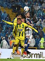 BOGOTA - COLOMBIA - 01 – 04 - 2018: Matias de los Santos (Der.) jugador de Millonarios salta a disputar el balón con Brayan Rovira (Izq.) jugador de Atletico Bucaramanga, durante partido de la fecha 12 entre Millonarios y Atletico Bucaramanga, por la Liga Aguila I 2018, jugado en el estadio Nemesio Camacho El Campin de la ciudad de Bogota. / Matias de los Santos (R) player of Millonarios jumps to vie the ball the ball with Brayan Rovira (L) player of Atletico Bucaramanga, during a match of the 12th date between Millonarios and Atletico Bucaramanga,  for the Liga Aguila I 2018 played at the Nemesio Camacho El Campin Stadium in Bogota city, Photo: VizzorImage / Luis Ramirez / Staff.