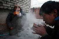 MONGOLIA. Ulaan Baatar. Battar (left), 55, eats breakfast on a bitterly cold winter morning. As the global financial crisis grips Asia, Mongolia is feeling the implications first hand as the country suffers from rising inflation pushing the price of food and fuel ever upwards. For the country's homeless, who live in sewers and abandoned garages in the capital and already face extreme discrimination and are denied access to basic health and social care, their lives are hanging in the balance. 2008