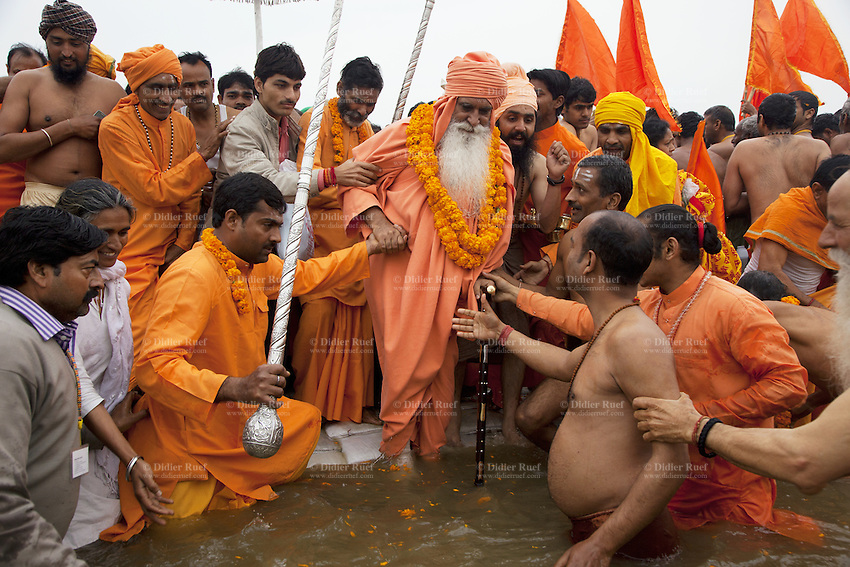 """India. Uttar Pradesh state. Allahabad. Maha Kumbh Mela. Royal bath on Basant Panchami Snan (fifth day of the new moon). The ritual """"Royal Bath"""" is timed to match an auspicious planetary alignment, when believers say spiritual energy flows to earth. A Guru wearing saffron clothes and a turban will take a dip in Sangam with his disciples and worships the river Ganges. The Kumbh Mela, believed to be the largest religious gathering is held every 12 years on the banks of the 'Sangam'- the confluence of the holy rivers Ganga, Yamuna and the mythical Saraswati. In 2013, it is estimated that nearly 80 million devotees took a bath in the water of the holy river Ganges. The belief is that bathing and taking a holy dip will wash and free one from all the past sins, get salvation and paves the way for Moksha (meaning liberation from the cycle of Life, Death and Rebirth). Bathing in the holy waters of Ganga is believed to be most auspicious at the time of Kumbh Mela, because the water is charged with positive healing effects and enhanced with electromagnetic radiations of the Sun, Moon and Jupiter. The Maha (great) Kumbh Mela, which comes after 12 Purna Kumbh Mela, or 144 years, is always held at Allahabad. Uttar Pradesh (abbreviated U.P.) is a state located in northern India. 15.02.13 © 2013 Didier Ruef"""