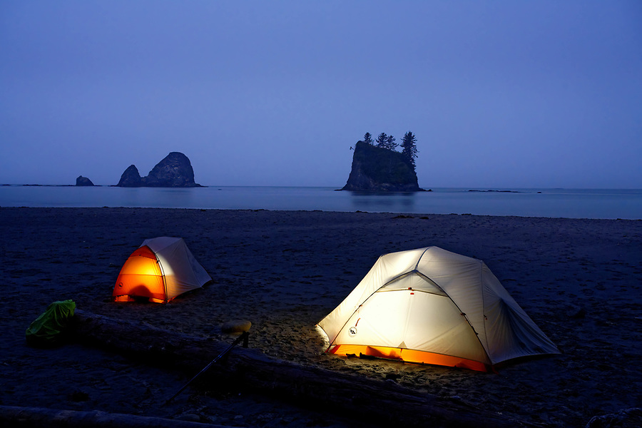 Glowing tents camping on beach below sea stack on Washington Coast, Scotts Bluff, Olympic National Park, Washington, USA