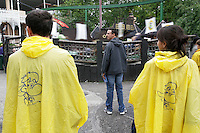 Italy. Province of Veneto. Castelnuovo del Garda. A couple of parents , wearing a yellow plastic rain coat with the figure of Prezzemolo, are waiting while their children are on the attraction: Peter pan. Prezzemolo (which means Parsley in english) is a green dragon and the symbol animal of Gardaland Gardaland is the biggest amusement park in Italy and one of the largest in the whole of Europe.  © 2006 Didier Ruef