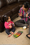 12 month old baby girl sitting on floor making music with mother