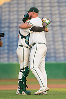 Tulane Green Wave pitcher Trent Johnson (42) hugs catcher Luis Aviles (21) after a game against the Houston Cougars on May 25, 2021 at BayCare Ballpark in Clearwater, Florida.  Tulane defeated Houston 4-1 in the opening game of the American Athletic Conference Tournament.  (Mike Janes/Four Seam Images)