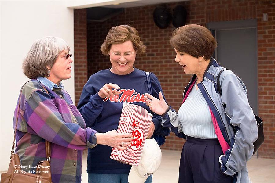 Three mature women with Ole Miss shirt enjoy popcorn at Mississippi University sport stadium in Oxford, Mississippi