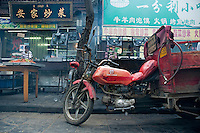Red motorbike parked in front of restaurants, Daqingzhen Si, Muslim District, Xian, Shaanxi, China.