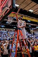 16 March 2019: University of Vermont Catamount Forward Anthony Lamb, a Junior from Toronto, Ontario, cuts himself a piece of net after a victory against the UMBC Retrievers in the America East Championship Game at Patrick Gymnasium in Burlington, Vermont. Lamb was named the Most Outstanding Player for the second time in his career with a game-high 28 points and nine rebounds as the Catamounts defeated the Retrievers 66-49, avenging their loss against the same team in last years' Championship Game. Mandatory Credit: Ed Wolfstein Photo *** RAW (NEF) Image File Available ***