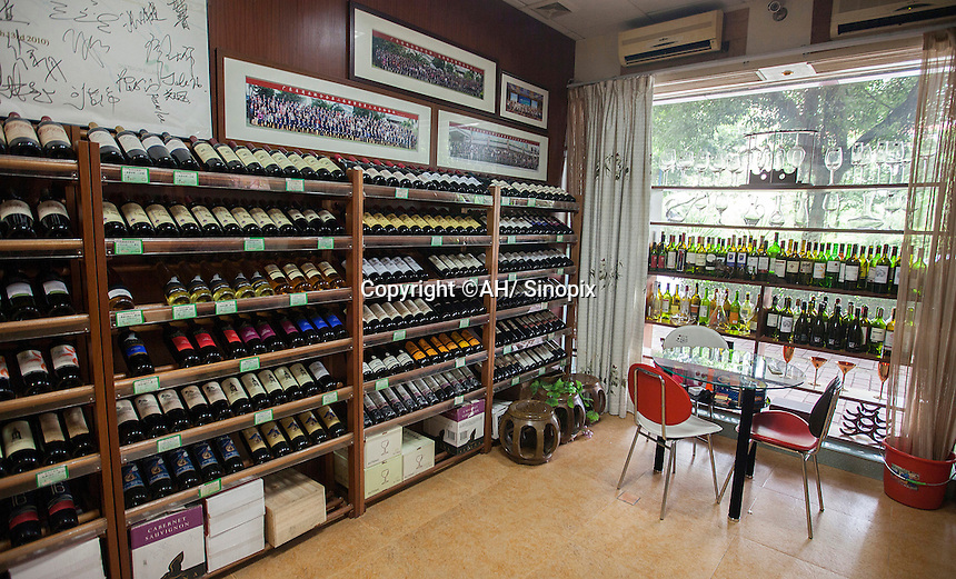 The interior of a shop that sells real and fake wine, Guangzhou, Guangdong Province, China, 18 July 2014. Collected empty bottles can be seen as they are often recycled into the Chinese underground fake wine industry.<br /> <br /> PHOTO BY SINOPIX