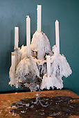 Brasilia, Brazil. Seven candles in a candlestick with artistic wax drippings.