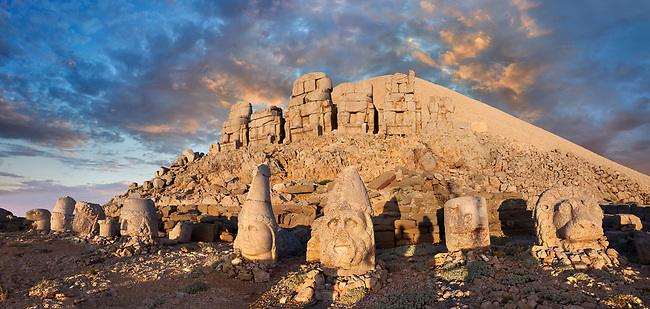 Statue heads at sunset, from right,  Lion, Eagle, Herekles, Apollo, Zeus, Commagene, Antiochus, & Eagle, with headless seated statues in front of the stone pyramid 62 BC Royal Tomb of King Antiochus I Theos of Commagene, east Terrace, Mount Nemrut or Nemrud Dagi summit, near Adıyaman, Turkey