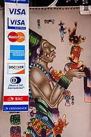 Chichicastenango, Guatemala.  Wall Hanging of a Mayan God, Credit Card Logos.