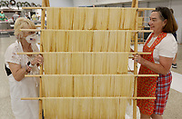 Cheryl Mitchell (left) and Elizabeth Pianalto move a full rack of fresh pasta noodles Thursday, July 15, 2021, into the drying area at the St. Joseph's Parish Hall in Tontitown. More than 3,000 pounds of pasta noodles are being prepared for the 122nd Tontitown Grape Festival which runs Tuesday, August 3 through Saturday, August 7. The homemade spaghetti will be served August 5 through 7. Check out nwaonline.com/210716Daily/ and nwadg.com/photos for a photo gallery.(NWA Democrat-Gazette/David Gottschalk)