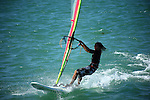 Windsurfing is a surface water sport that combines elements of surfing and sailing.