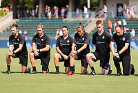 CARY, NC - SEPTEMBER 12: Portland Thorns assistant coach Rich Gunney, head athletic trainer Pierre Soubrier, assistant coach Sophie Clough, goalkeeping coach Nadine Angerer, performance specialist Tom Milroy, and head coach Mark Parsons kneel during the national anthem before a game between Portland Thorns FC and North Carolina Courage at WakeMed Soccer Park on September 12, 2021 in Cary, North Carolina.