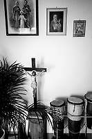 Switzerland. Canton Ticino. Grancia. Various objets in the house of Don Gerald Chukwudi Ani, a catholic priest from Nigeria. On the wall, a few religious paintings. On the ground, a wooden crucifix with Jesus Christ on the cross. Nigerian drums. Grancia is a municipality in the district of Lugano. 7.03.2020  © 2020 Didier Ruef