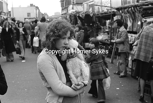 Tower Hamlets, London. 1975<br /> A young girl and a much-loved poodle in the Roman Road Market. The market is the heart of Bow, and 'going down the Roman' has been a tradition for generations. 1970s UK