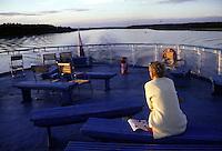 RUSSIA  Viaggio in battello da San Pietroburgo a Mosca lungo il Volga. Una turista sul ponte del battello al tramonto osserva il panorama sul fiume e le sue rive.